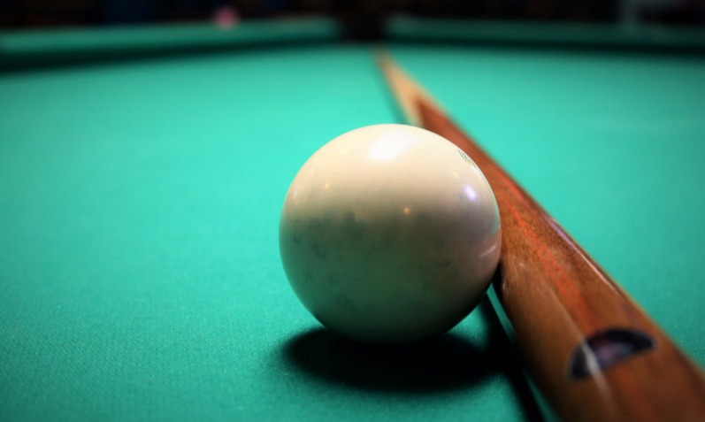 Pool stick on table with cue ball